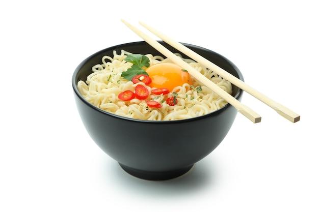 Kom gekookte noedels met kruiden en eetstokjes die op witte achtergrond worden geïsoleerd