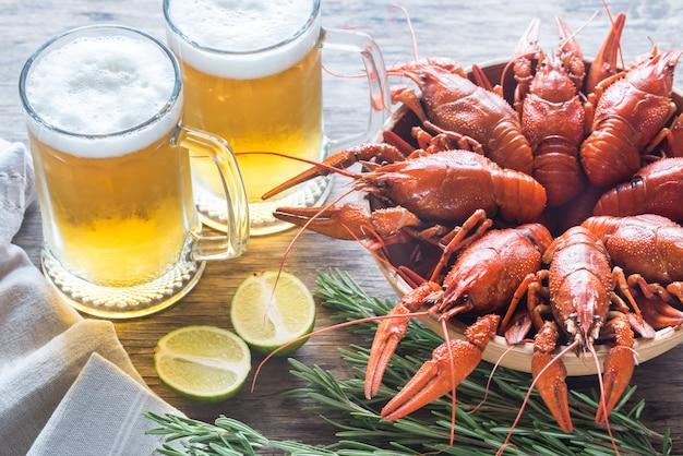 Kom gekookte rivierkreeft met twee mokken bier