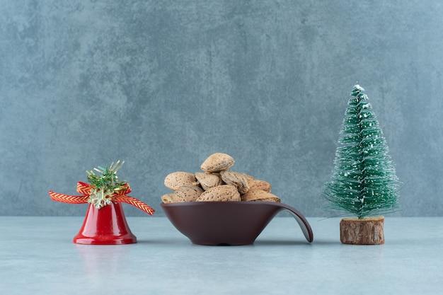 Kom gepelde amandelen en kerstversieringen op marmer.