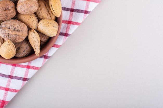 Kom gepelde organische amandelen en okkernoten op witte achtergrond. hoge kwaliteit foto