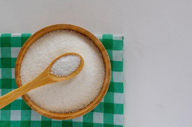 Kom geraffineerde suiker op een groen en wit geruit tafelkleed. bovenaanzicht