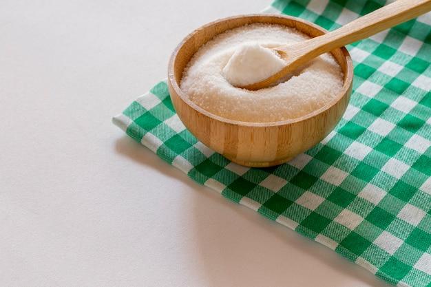 Kom geraffineerde suiker op een groen en wit geruit tafelkleed. hoek van 45 graden