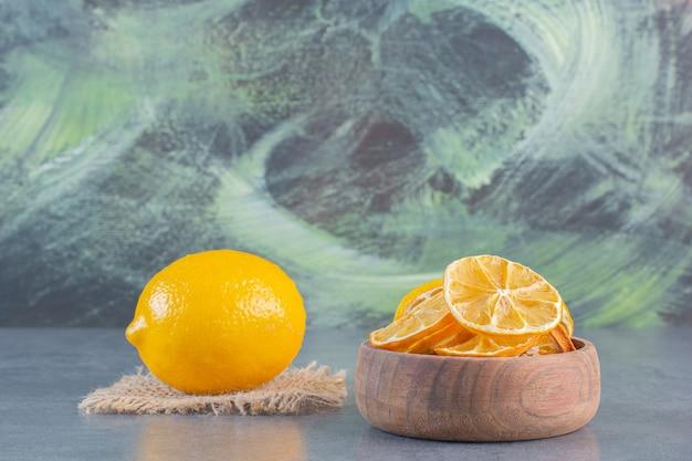 Kom gesneden citroenen en hele citroen op stenen oppervlak