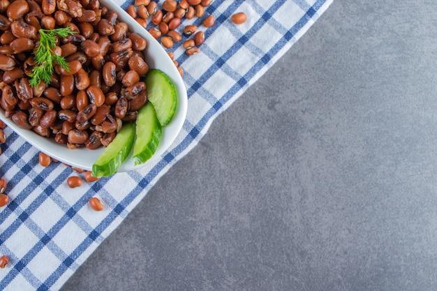 Kom gesneden komkommer en bonen op een handdoek, op de marmeren achtergrond.