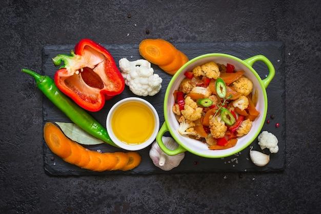 Kom gestoofde groentenragoût en ruwe ingrediënten. gezond, vegetarisch voedselconcept