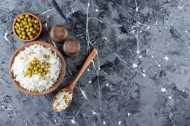 Kom gestoomde witte rijst met groene erwten op marmeren achtergrond.
