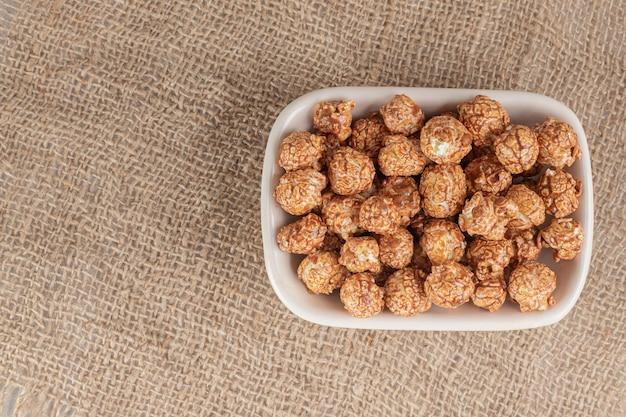 Kom gevuld met bruine gekonfijte popcorn op textiele tafel.