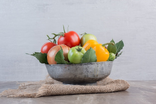 Kom gevuld met paprika, ui, rode tomaten, groene tomaten, komkommer, rode ui en bladeren, op marmer.