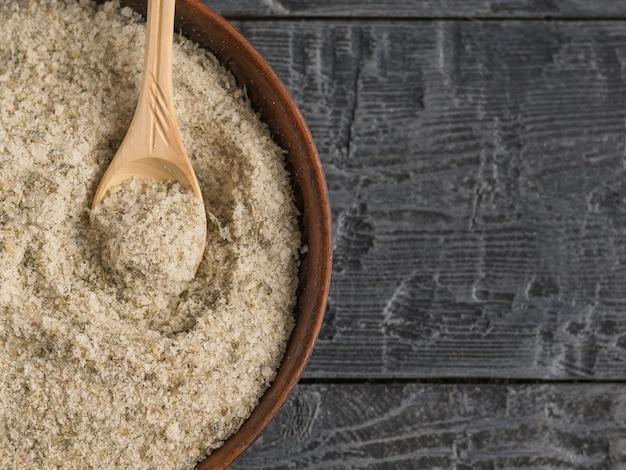 Kom gevuld met zout met kruiden en een eetlepel licht hout op de tafel. het uitzicht vanaf de top.