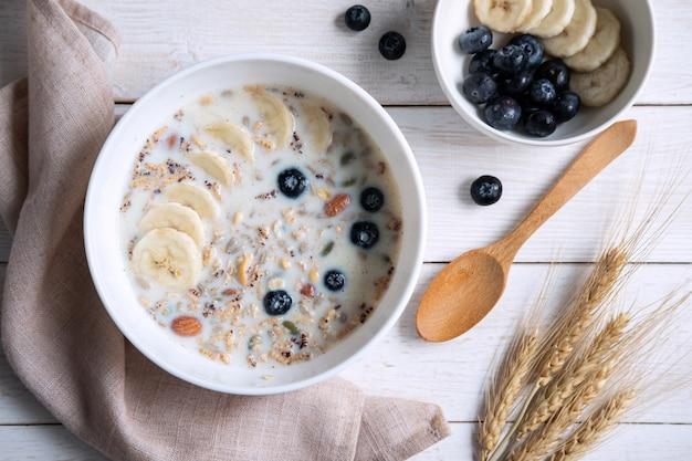 Kom granolaamandel en korrels met bosbes en banaan op houten lijst, gezond ontbijt