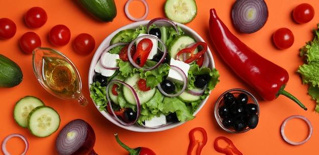 Kom griekse salade en ingrediënten op sinaasappel
