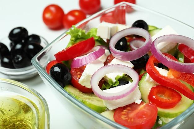 Kom griekse salade en ingrediënten op wit