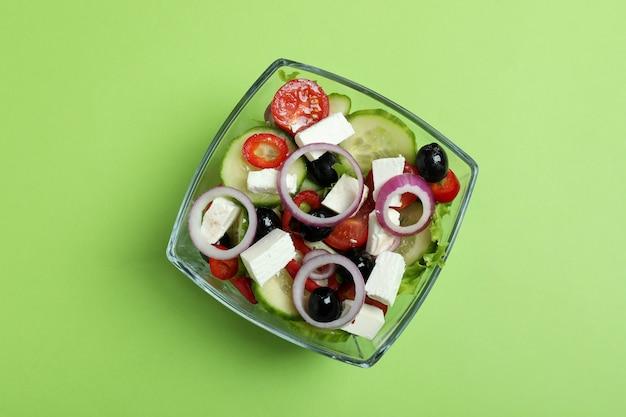 Kom griekse salade op groene ondergrond, bovenaanzicht