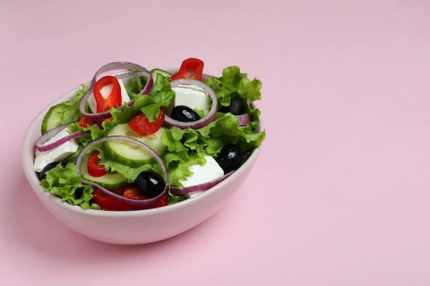 Kom griekse salade op roze oppervlak