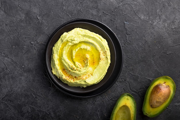 Kom groene hummus, heerlijke room van kikkererwten en avocado op een stenen oppervlak.