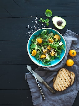 Kom groene salade met avocado, rucola, kerstomaatjes en zonnebloempitten, gegrilde gekweekte plakjes en verse kruiden
