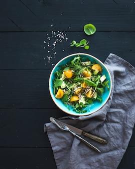 Kom groene salade met avocado, rucola, kerstomaatjes en zonnebloempitten, gegrilde gekweekte plakjes, verse kruiden over zwart houten oppervlak