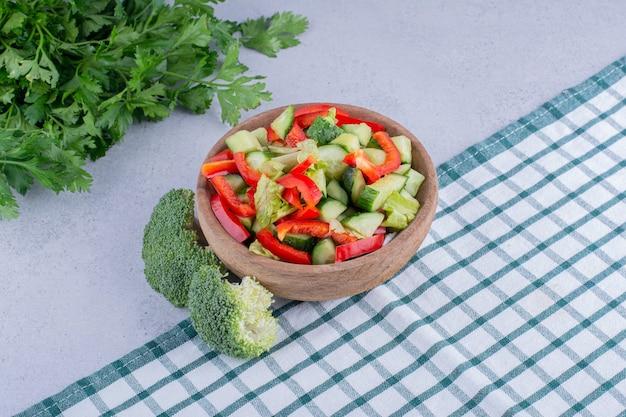 Kom groentesalade, bundel peterselie en broccoli op marmeren achtergrond. hoge kwaliteit foto
