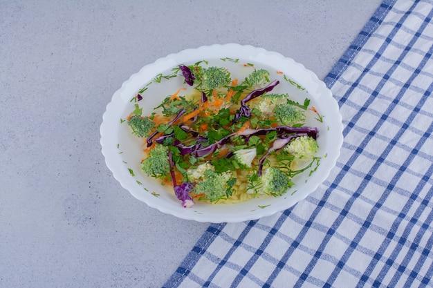 Kom groentesalade gemengd met dille op marmeren achtergrond.
