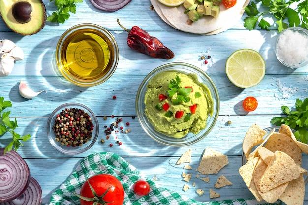 Kom guacamole en ingrediënten op blauwe achtergrond. bovenaanzicht.