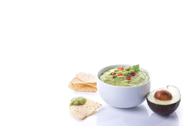 Kom guacamole met avocado en nacho's geïsoleerd op een witte achtergrond met kopie ruimte.