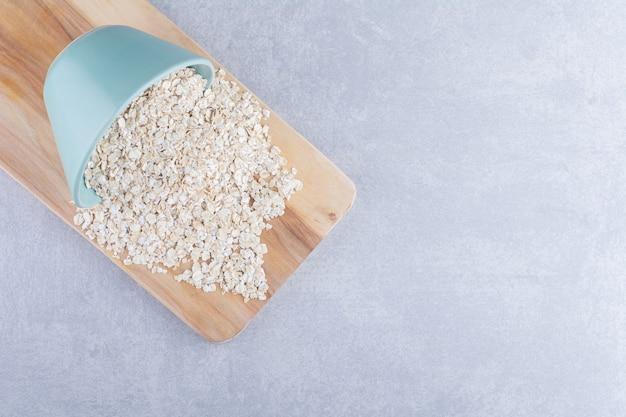 Kom haver gemorst over een houten dienblad op marmeren oppervlak