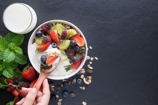 Kom havergranola met yoghurt, verse moerbei, aardbeien, kiwimunt en notenbord voor gezond ontbijt, bovenaanzicht, kopieerruimte, plat gelegd. lepel in de handen van vrouwen. vegetarisch voedselconcept.