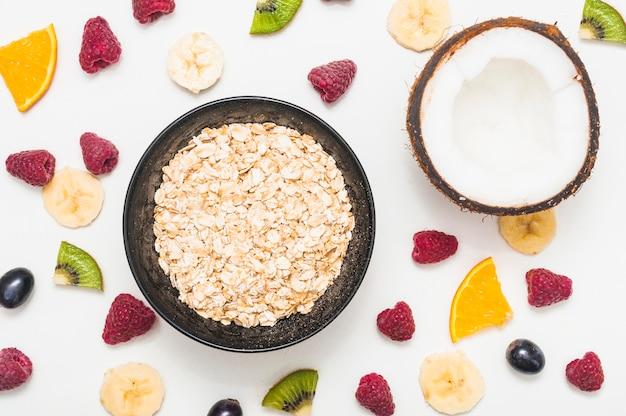 Kom havervlokken met gehalveerde kokosnoot en kleurrijke fruitplakken