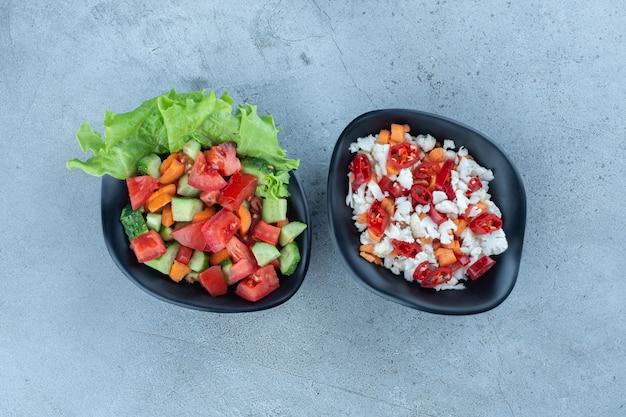 Kom herderssalade naast een kom peper en bloemkoolsalade op marmeren oppervlakte