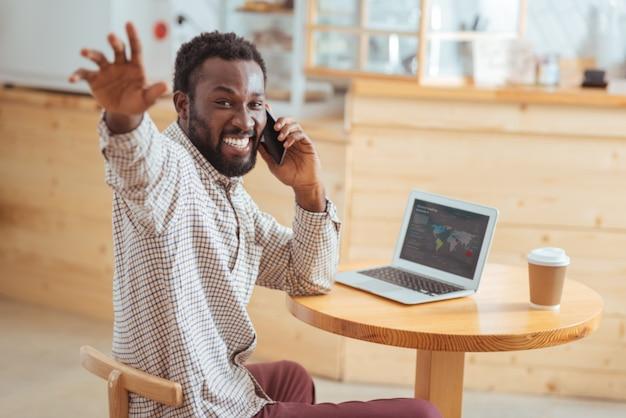 Kom hier. vrolijke jongeman zit aan de tafel in café voor een laptop, praat aan de telefoon en zwaait naar iemand, begroet hem en nodigt uit om langs te komen terwijl hij glimlacht