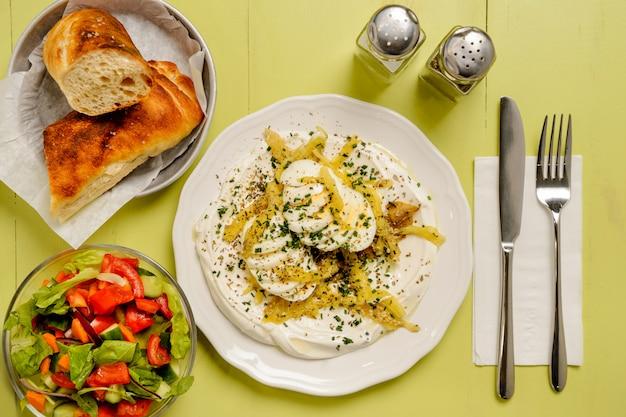 Kom hummus met gesneden ei bovenop. salade en brood op een groene houten tafel. veganistische snack. bovenaanzicht