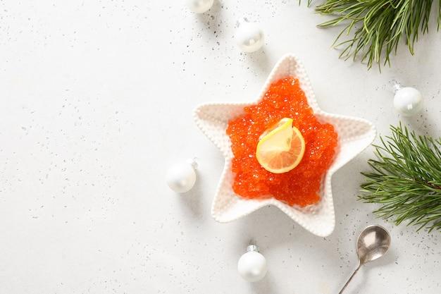 Kom in vorm van ster met rode kaviaar die voor het feestelijke diner van kerstmis op witte lijst wordt gediend. uitzicht van boven. ruimte voor tekst.