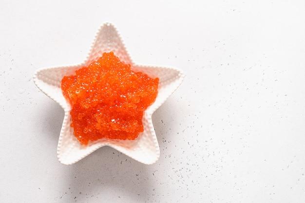 Kom in vorm van ster met rode kaviaar op witte lijst. uitzicht van boven. ruimte voor tekst.