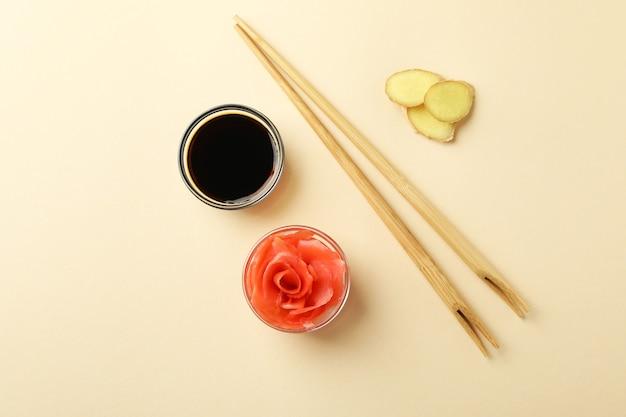 Kom ingelegde gember, sojasaus en eetstokjes op beige ondergrond