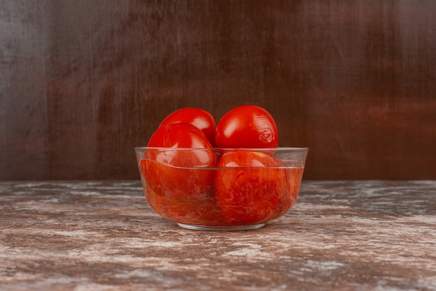 Kom ingelegde tomaten op marmeren oppervlak.