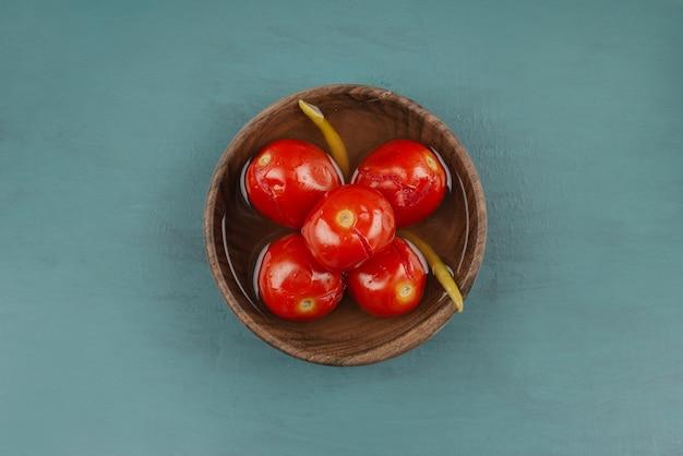 Kom ingelegde tomaten op marmeren tafel.