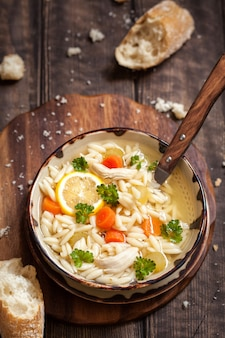 Kom italiaanse citroen kip orzo soep. rustieke stijl