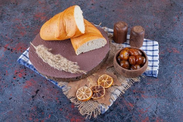 Kom jam en brood op een bord op een theedoek, op het blauwe oppervlak. .