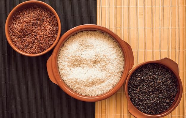 Kom jasmijn rode rijst; witte rijst en zwarte rijstkommen op onderleggertje