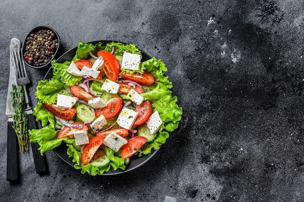 Kom kant-en-klare griekse salade. zwarte achtergrond. bovenaanzicht. ruimte kopiëren.