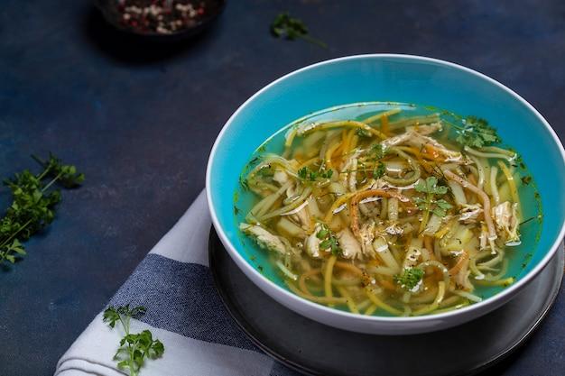 Kom kippensoep met vermicelli, kruiden en groenten