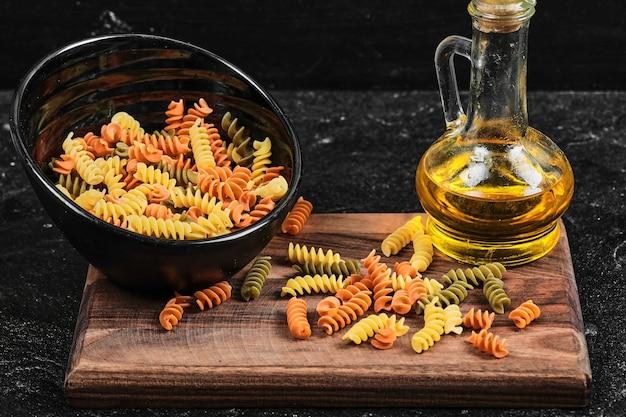 Kom kleurrijke fusilli pasta en fles olie op donkere tafel.