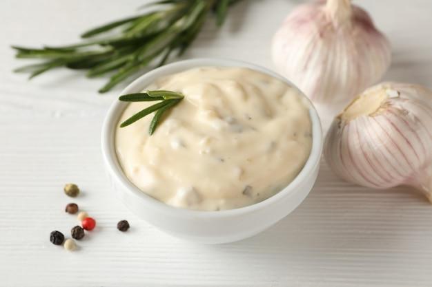Kom knoflooksaus, ingrediënten op wit