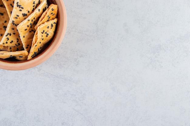 Kom krokante crackers met zwarte zaden op marmeren achtergrond.