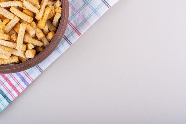 Kom lekkere knapperige crackers met tafellaken op marmeren achtergrond. hoge kwaliteit foto