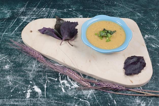 Kom linzensoep met basilicum op een houten bord.