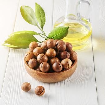 Kom macadamia-noten met een fles macadamia-olie op een witte lijst.