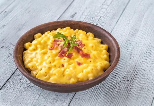 Kom macaroni en kaas met plakjes gebakken spek