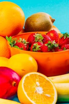 Kom met aardbeien; oranje; kiwi en banaan op blauwe achtergrond