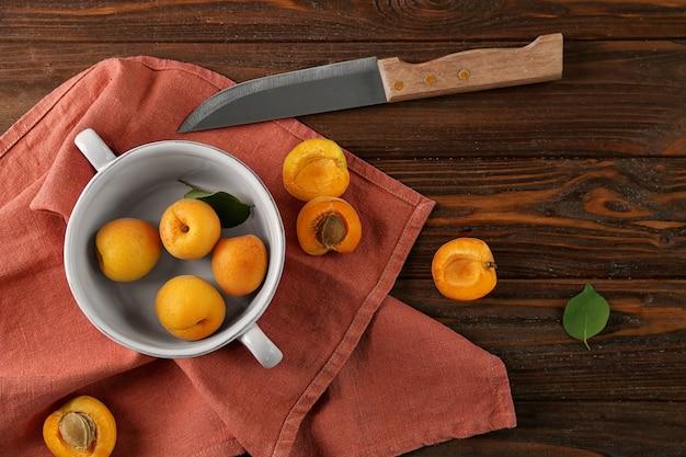 Kom met abrikozen en mes op rood servet